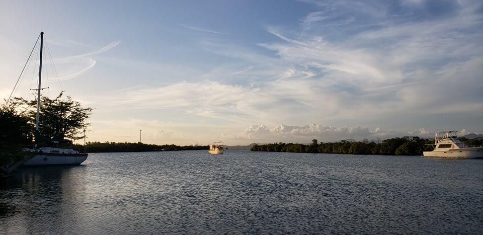 Mar conectado con un cielo azul con nubes suaves blancas y varias embarcaciones.