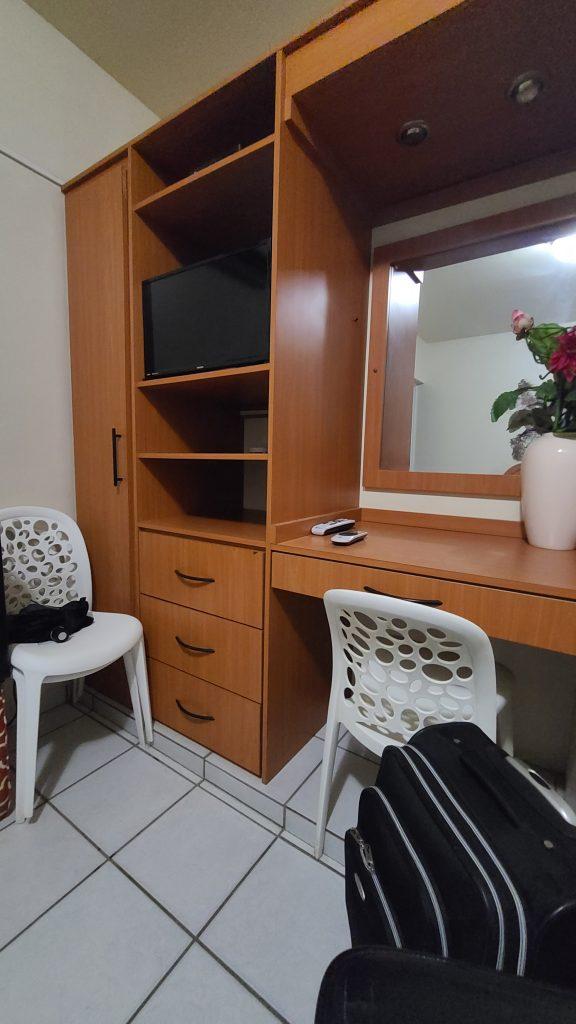 En habilitación mueble con varios espacios y gavetas de madera donde esta un televisor, un espejo, y al frente dos sillas blancas.