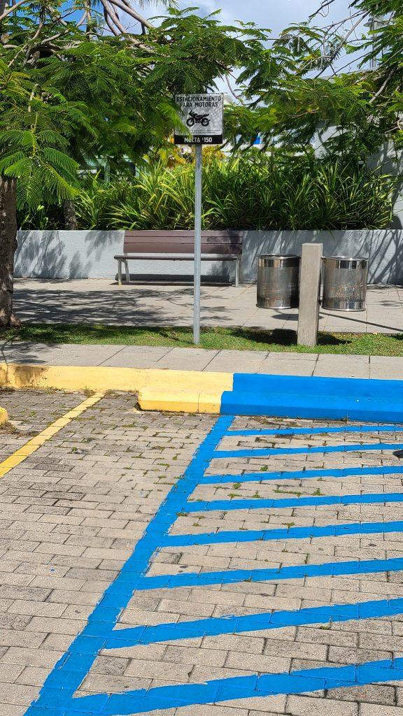 área pintada de amarilla que indica espacio para estacionarse motoras y parte del área de abordaje del estacionamiento reservado para personas con discapacidades.
